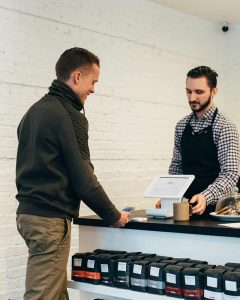 man buying coffee from sales assistant